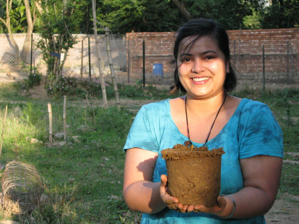 A volunteer at Peepal Farm with the Cow Dung Pot