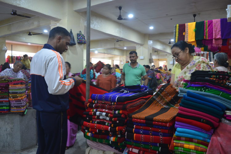 Male customers intrigued with the beautifully woven handlooms | Image courtesy: Milaap