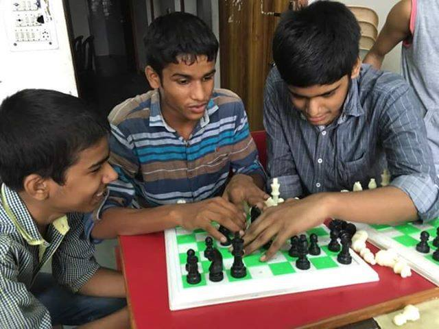 Students learning enthusiastically with a volunteer | Image Courtesy : Project Checkmate